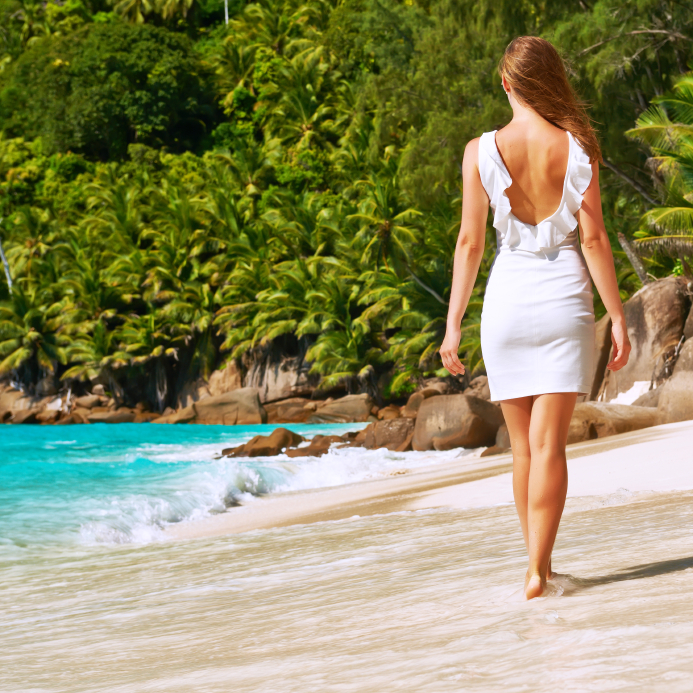 Woman wearing dress on beach at Seychelles
